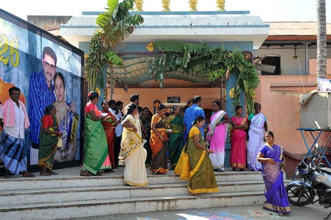 Bröllopsgäster utanför festen. OBS! den gigantiska skylten med brudparet.
